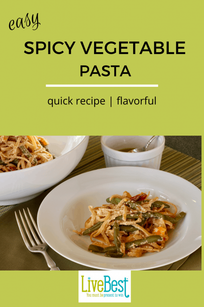 bowl of spicy vegetable pasta with ramekin of chile oil nearby