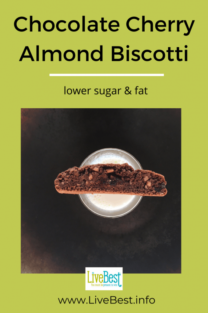 one chocolate cherry biscotti perched on a glass of milk