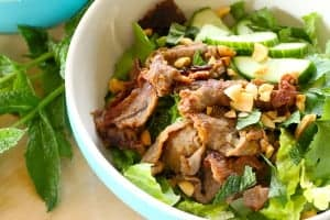 bowl with beef, peanuts, lettuce, cucumbers, basil and rice noodles