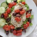 plate of herbed chicken with cooked tomatoes and kalamate olive over lettuce and cucumbers