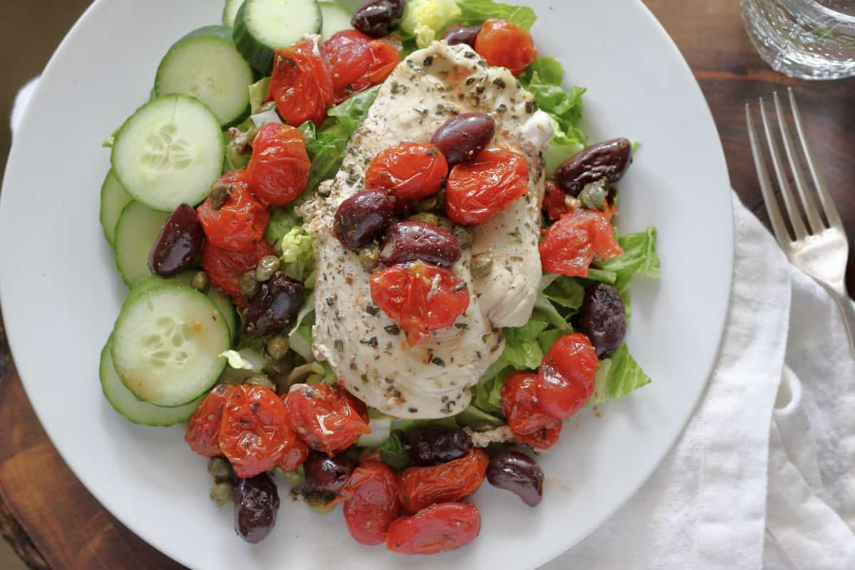 30-minute meal with herbed chicken, tomatoes, olive, and capers poured over crisp lettuce and cucumbers