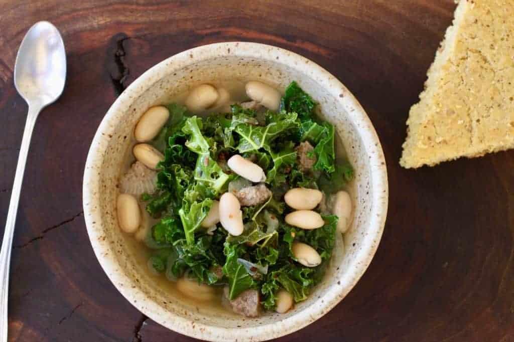 bowl of Kale Turkey White Bean Soup and cornbread wedge