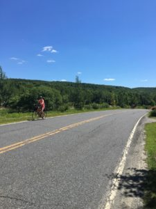 a woman biking on a 2 lane road in eastern Canada, photo by Judy Barbe, LiveBest.info