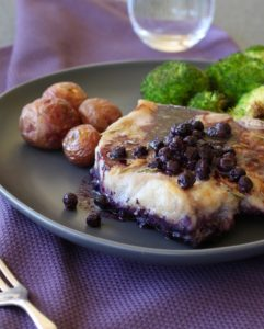 Baked Blueberry Pork Chops on plate with potatoes and broccoli