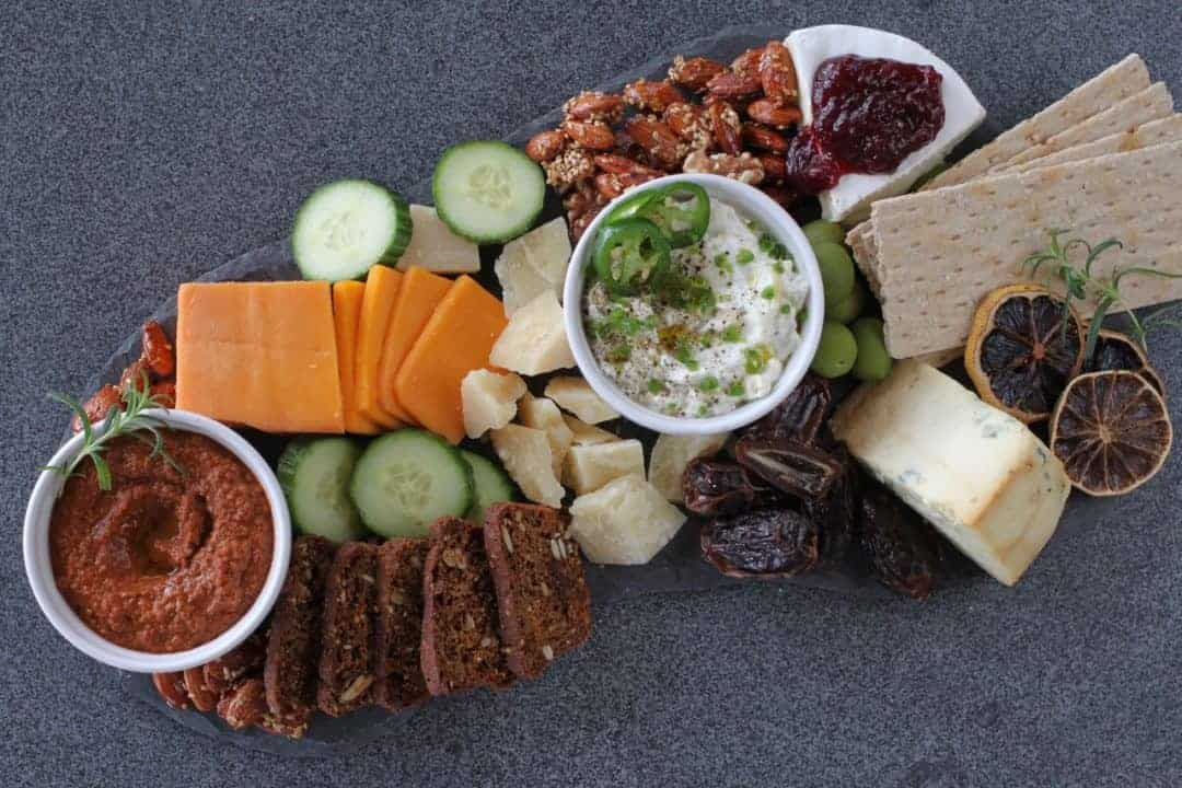 cheese board with dips, crackers and vegetables