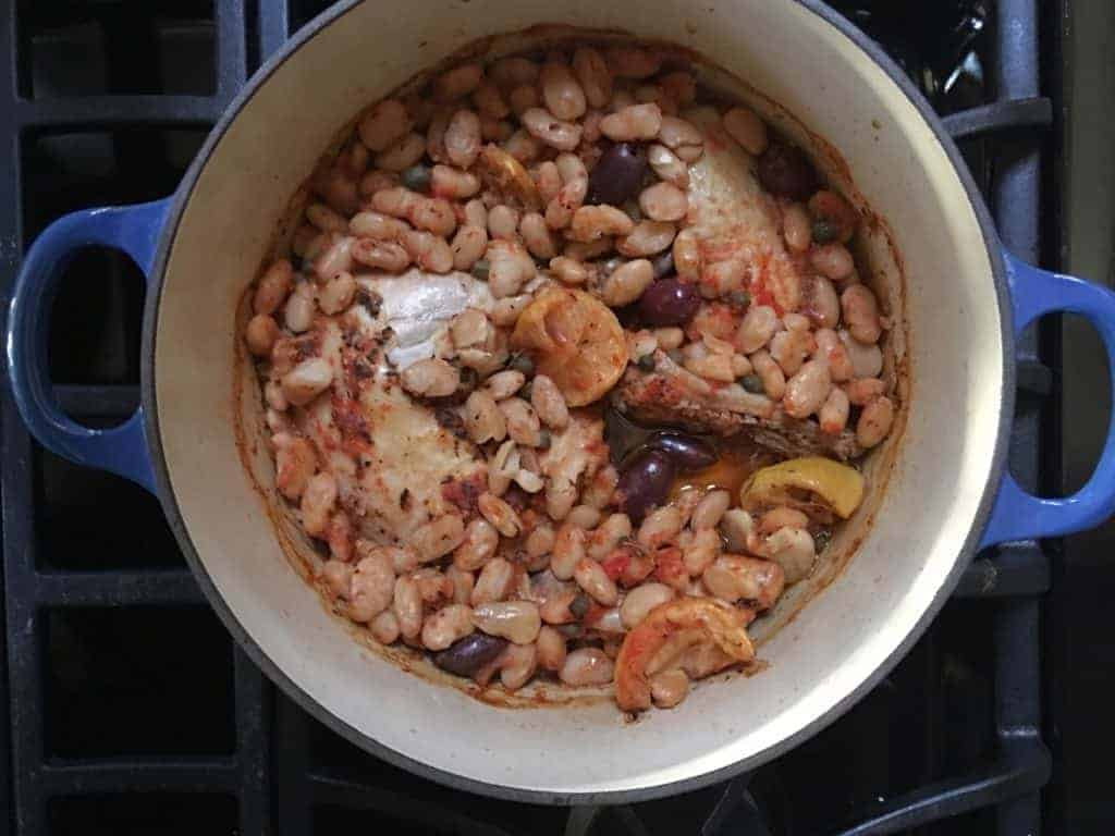 pot of One-pot Baked Greek Chicken Stew is bursting with flavor. Olives, tomatoes, capers, garlic, and beans