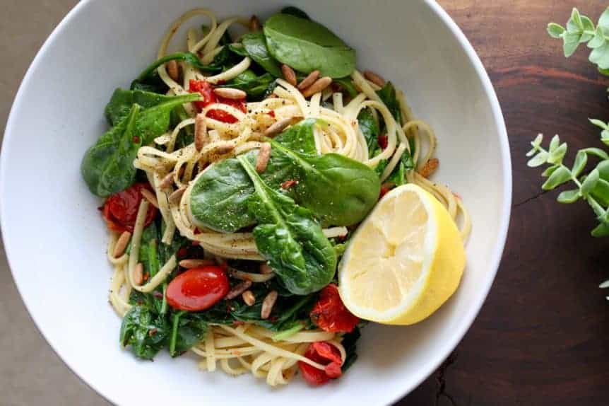 a bowl of spaghetti with spinach, blistered tomatoes and pine nuts