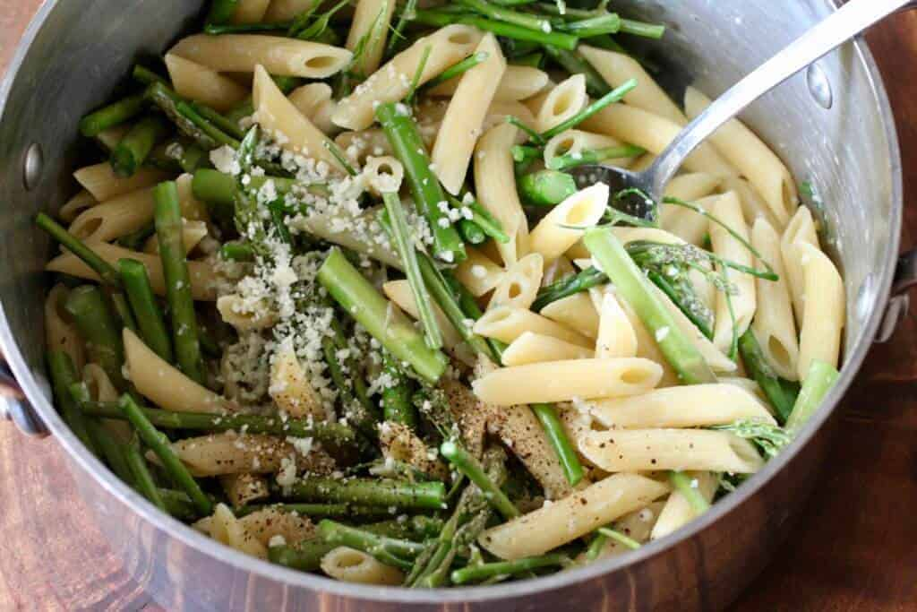 cooking pot with penne pasta and asparagus