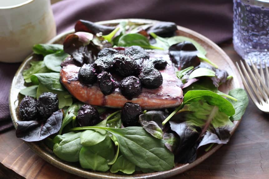 salmon fillet with caramelized grapes on fresh spinach