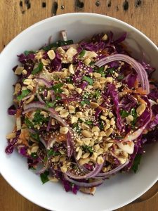 Bowl of Asian Sesame Chicken Salad topped with roasted peanuts