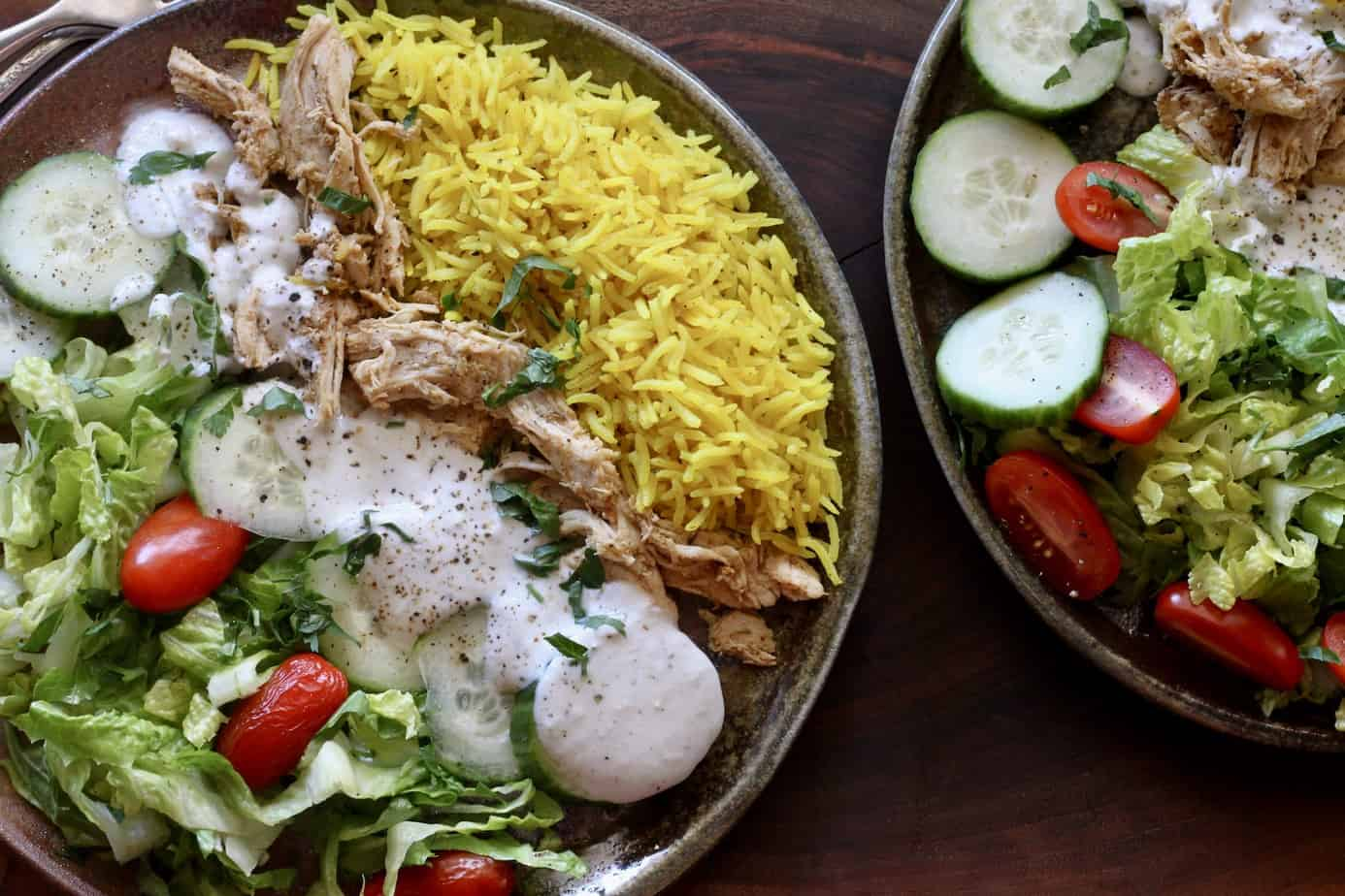 2 plates with chicken with rice and creamy yogurt sauce
