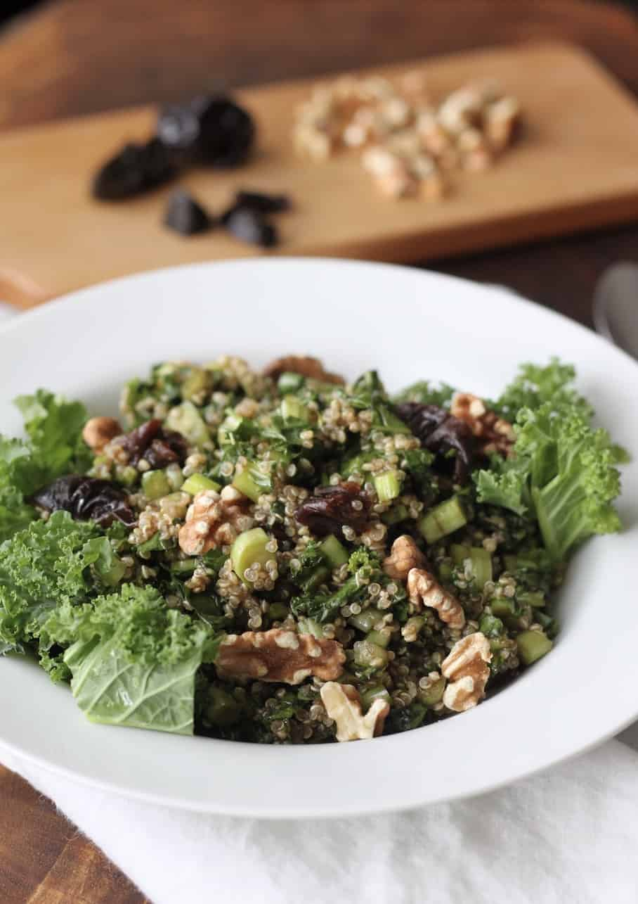 Bowl of kale, quinoa salad with fruit and nuts in background.