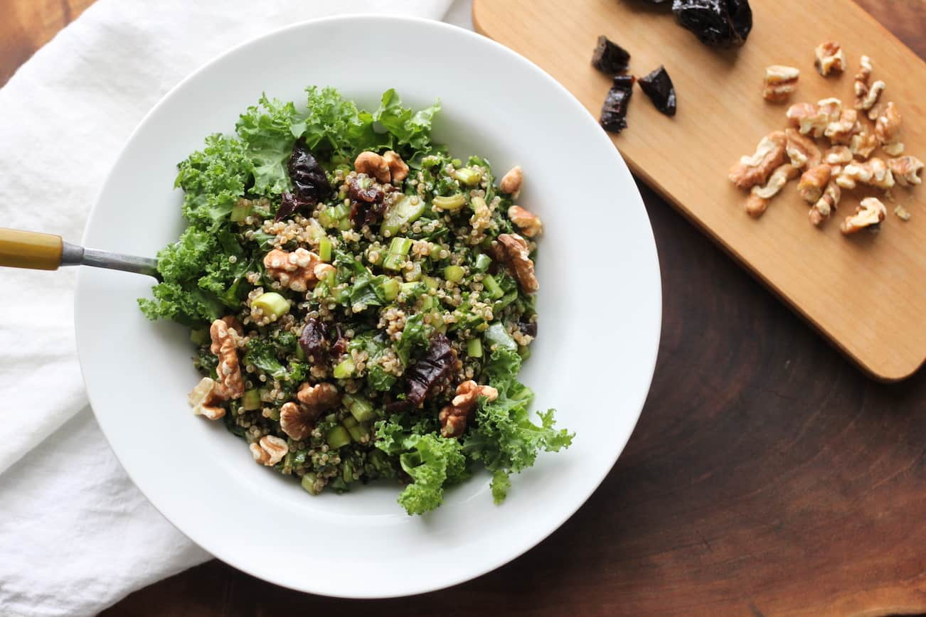 bowl of kale quinoa salad with walnuts and chopped prunes