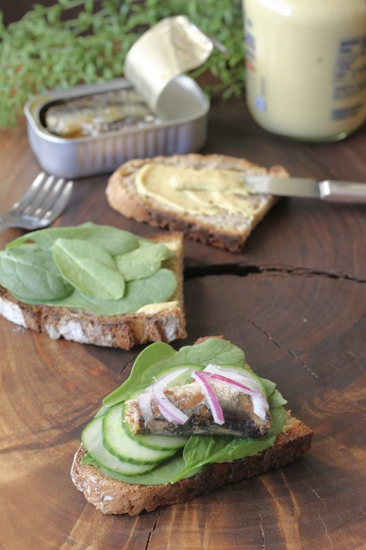 Here's how to make an open-faced sardine sandwich. Mustard, spinach, cucumber, sardines and red onion.