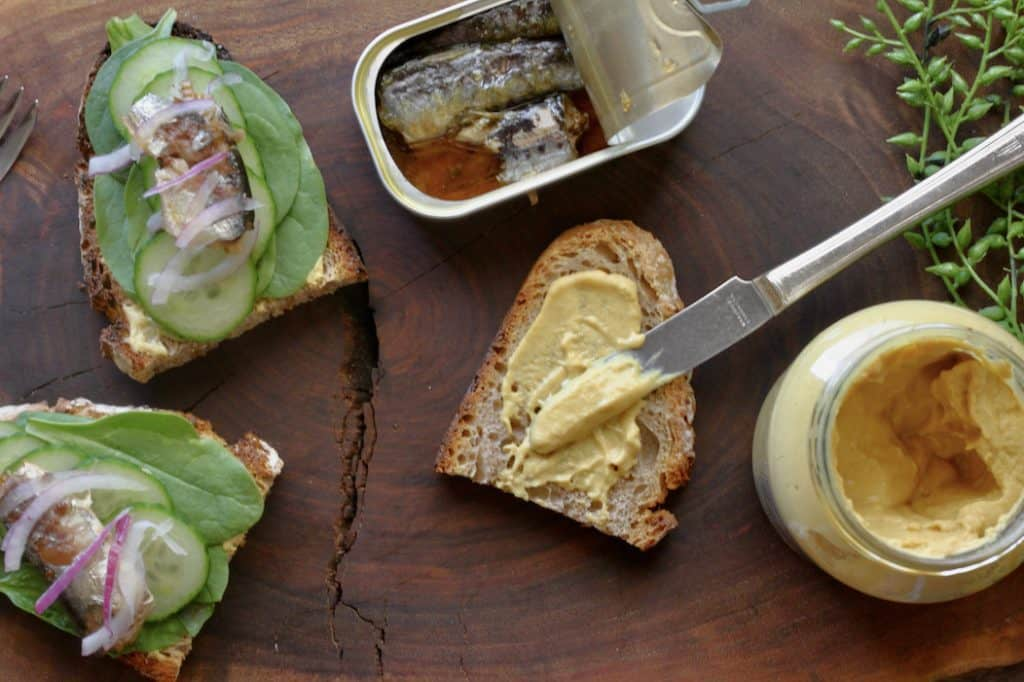 slices of bread with spinach leaves, cucumber slices and sardines with mustard