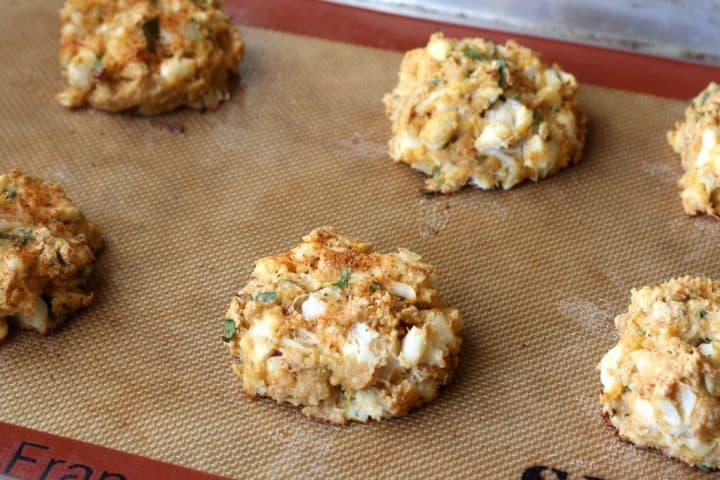 six baked crab cakes on a baking sheet pan