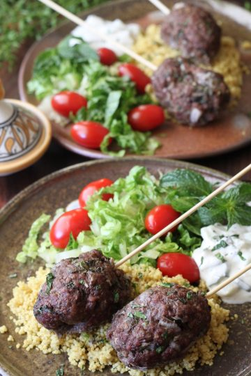 2 plates with ground beef kabobs with lettuce, tomato and couscous and cucumber yogurt sauce.
